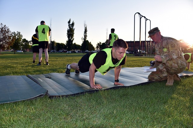 Sgt. Zach Sheely, 100th Missile Defense Brigade, grades Staff Sgt. Kendall Feb, Company C, 53rd Signal Battalion, 1st Space Brigade, during the Army Physical Fitness Test portion of the U.S. Army Space and Missile Defense Command/Army Forces Strategic Command's 2018 Best Warrior Competition June 4 at Fort Carson, Colorado. Feb was named the SMDC Noncommissioned Officer Best Warrior for 2018.