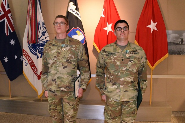 Staff Sgt. Kendall Feb, Company C, 53rd Signal Battalion, left, and Spc. Dylan S. Caramella, Company B, 53rd Signal Battalion, become the U.S. Army Space and Missile Defense Command/Army Forces Strategic Command 2018 Best Warriors during a ceremony at the command's Peterson Air Force Base, Colorado, headquarters June 7.