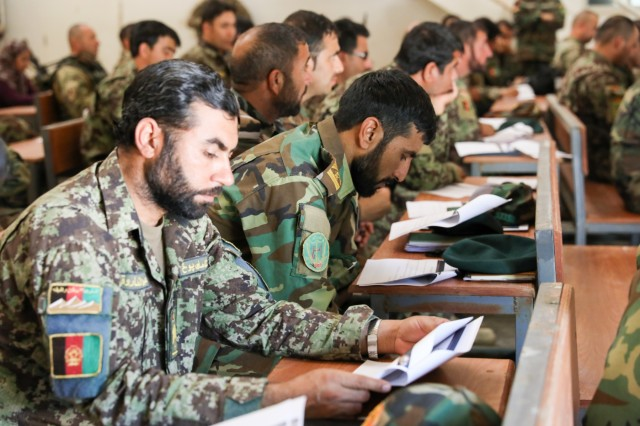 Senior enlisted Afghan leaders look at a presentation, May 31, 2018, during a senior enlisted leader huddle put together by Command Sgt. Maj. Joe Derma, senior enlisted leader for the Military Advisory Team for TAAC-South, in Kandahar, Afghanistan.