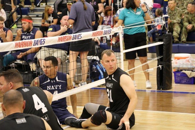 U.S. Army veteran Capt. Tim Bomke waits for his teammate to serve the ball during sitting volleyball bracket play against Team Navy June 4, 2018, in the Cadet East Gymnasium at the U.S. Air Force Academy during the 2018 Department of Defense Warrior Games. The DoD Warrior Games are conducted from June 1 - 9. It is an adaptive sports competition for wounded, ill and injured service members and veterans. Approximately 300 athletes representing teams from the Army, Marine Corps, Navy, Air Force, Special Operations Command, United Kingdom Armed Forces, Canadian Armed Forces, and the Australian Defence Force will compete in archery, cycling, track, field, shooting, sitting volleyball, swimming, wheelchair basketball, and - new this year - powerlifting and indoor rowing. (U.S. Army photo by Robert Whetstone)