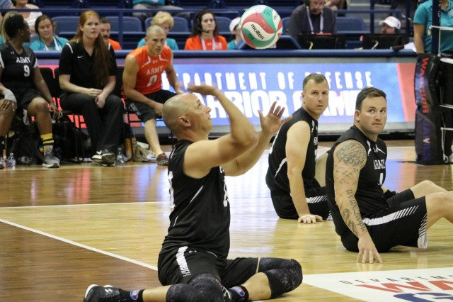 U.S. Army Sgt. 1st Class Daniel Ohlinger serves the ball into play during the sitting volleyball bronze medal match against Team SOCOM June 8, 2018, in Clune Arena at the U.S. Air Force Academy during the 2018 Department of Defense Warrior Games. The DoD Warrior Games are conducted from June 1 - 9. It is an adaptive sports competition for wounded, ill and injured service members and veterans. Approximately 300 athletes representing teams from the Army, Marine Corps, Navy, Air Force, Special Operations Command, United Kingdom Armed Forces, Canadian Armed Forces, and the Australian Defence Force will compete in archery, cycling, track, field, shooting, sitting volleyball, swimming, wheelchair basketball, and - new this year - powerlifting and indoor rowing. (U.S. Army photo by Robert Whetstone)
