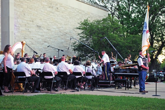 Chief Warrant Officer 2 Matthew David, commander of the 1st Infantry Division Band, conducts the combined military musicians and Salina Symphony for several patriotic songs played during the June 2 Symphony at Sunset concert in Abilene, Kansas. The annual event is held to commemorate D-Day and is a three-way partnership between the 1st Inf. Div. Band, the Salina Symphony and the Eisenhower Presidential Library, Museum and Boyhood Home. Nearly 6,000 people attended the event held on the library lawn.