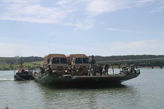 180609-Z-NM086-0312: Soldiers of the South Dakota Army National Guard's 200th Engineer Company ride on an improved ribbon bridge (IRB) while transporting vehicles across the Missouri River during the Golden Coyote training exercise, Chamberlain, S.D., June 9, 2018. Two bridge erection boats are used to maneuver the IRB across a body of water to complete the river crossing.
