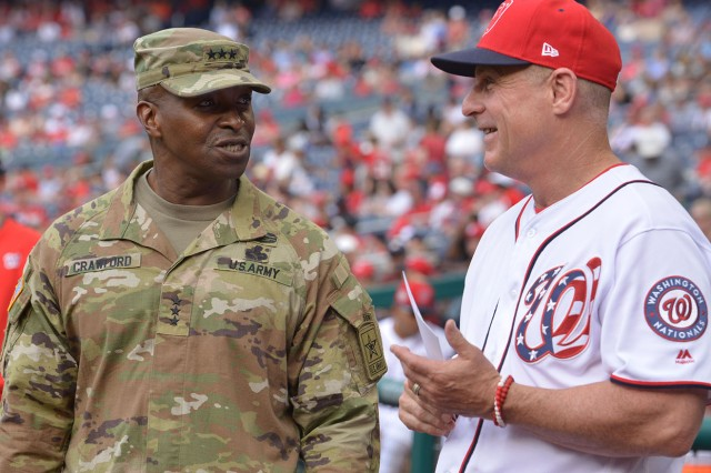 Lt. Gen. Bruce Crawford, Chief Information officer of the Army, talks with Washington Nationals bench coach Chip Hale on June 10, 2018.