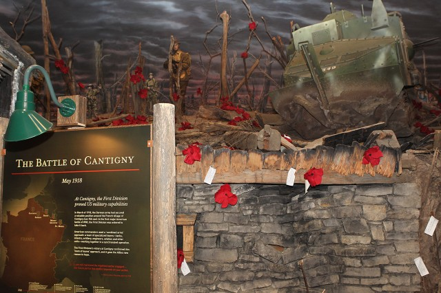 Poppy flowers and names of Soldiers that died during the Battle of Cantigny are displayed in the First Division Museum in Wheaton, Illinois, May 28, during the commemoration of the first battle won by American forces during World War I. The scene depicts the 1st Infantry Division Soldiers as they enter the battle torn town of Cantigny, France.