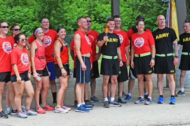 Fort Riley Military Police, USAG Fort Riley, Kansas, accept the torch from Riley County police at the Ogden Gate, May 31. The MPs ran the torch across Fort Riley before handing it off to members of the Junction City Police Department and Special Olympians.