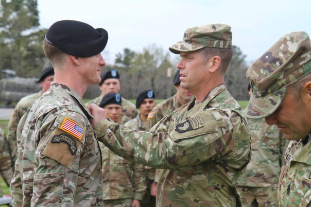 Col. John Cogbill pins the coveted Air Assault Badge on Capt. John Bergman, from 1st Battalion, 187th Infantry Regiment.  Capt. John Bergman was the Honor Graduate and Ruck March Champion of his Air Assault School Class, on Fort Campbell, KY.