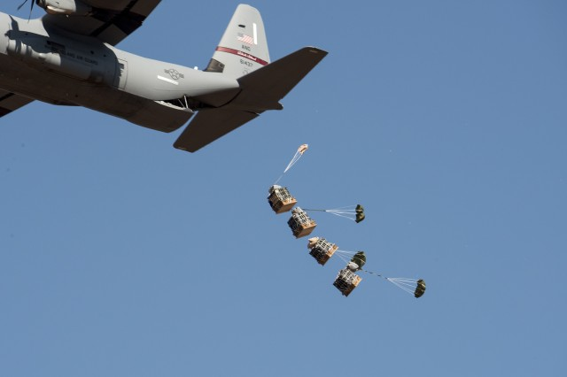 A stick of four Extracted High and Low Speed Container Delivery System (EHLSCDS) bundles are extracted from a U.S. Air Force C-130J aircraft during low speed airdrop operational testing.