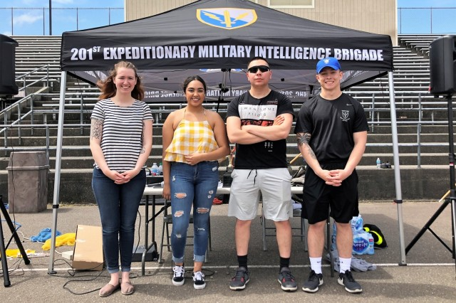 "Soldiers from the 201st Expeditionary Military Intelligence Brigade's Junior Enlisted Council stand together for a picture following the brigade's organizational day May 24, 2018, at Cowan Stadium, on Joint Base Lewis-McChord, Washington. Pictured, left to right, are Spc. Shelby Weaver, JEC President; Pfc. Sabrina Lopez, JEC Media Manager; Spc. Marty Martinez, JEC Vice President; and Spc. Nicholas Seaman-Boyce, JEC Treasurer. ""Org Days"" allow the brigade and its subordinate units, their families, and leaders to compete against each other in a relaxed environment while improving morale and strengthening unit cohesion. While many units across the Army hold org days, what made this one unique was that it put together entirely by the 201st EMIB's Junior Enlisted Council, from the planning stages to the execution. (U.S. Army photo by Staff Sgt. Chris McCullough)"