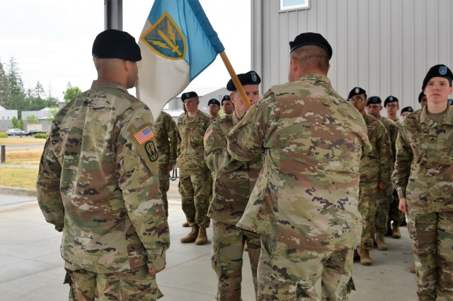 "Master Sgt. Kyle Strate hands the Headquarters & Headquarters Company guidon to 1st Sgt. Roger Dover during the company Change of Responsibility ceremony held June 8, 2018, in the ""Hellhounds"" Company Operations Facility (COF), on Joint Base Lewis-McChord, Washington.  The ceremony was held to say farewell to 1st Sgt. Dover, the outgoing senior enlisted leader for Headquarters and Headquarters Company, and welcome 1st Sgt. Hudson, the incoming senior enlisted leader for the Hellhounds Company.  (U.S. Army photo by Staff Sgt. Chris McCullough)"