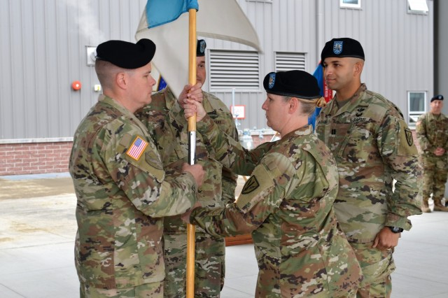 """1st Sgt. Theresa Hudson hands the Headquarters & Headquarters Company guidon to  Master Sgt. Kyle Strate during the company Change of Responsibility ceremony held June 8, 2018, in the """"Hellhounds"""" Company Operations Facility (COF), on Joint Base Lewis-McChord, Washington.  The ceremony was held to say farewell to 1st Sgt. Dover, the outgoing senior enlisted leader for Headquarters and Headquarters Company, and welcome 1st Sgt. Hudson, the incoming senior enlisted leader for the Hellhounds Company.  (U.S. Army photo by Staff Sgt. Chris McCullough)"""