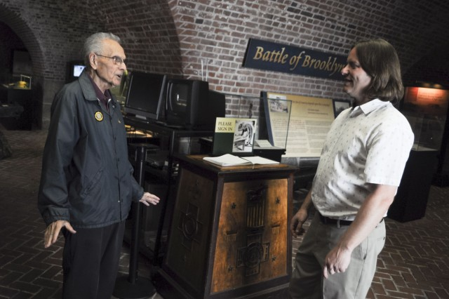 Justin Batt (right), director, Harbor Defense Museum, Fort Hamilton, New York, talks with Tom Trombone, museum volunteer, May 9, 2018.