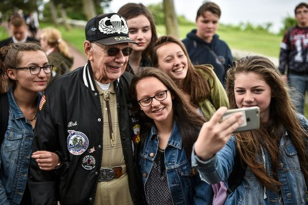 U.S. Army World War II Veteran Robert DeVinney poses for a selfie with French school kids, June 1, 2018, at the American Cemetery and Memorial, Normandy, France. DeVinney fought in the Battle of the Bulge, the last German offensive during World War II. He was a private first class assigned to Hotel Company, 3rd Battalion, 504th Regiment, 82nd Airborne Division.