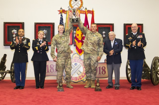 (Center) Staff Sgt. Ryan Essenmacher, an explosive ordnance disposal team leader with 720th Ordnance Company from Baumholder, Germany, and his team member, 1st. Lt. Jesse Way, receive the 2018 Ordnance Crucible - EOD Team of the Year trophy during the event's closing ceremony at Fort Lee, Va., June 9, 2018. EOD teams are assessed on operations and associated tasks required to provide EOD support to unified land operations to eliminate and/or reduce explosive threats. The Ordnance Crucible is designed to test Soldiers' teamwork and critical thinking skills as they apply technical solutions to real world problems improving readiness of the force. (U.S. Army photo by Staff Sgt. Lance Pounds, 71st Ordnance Group (EOD), Public Affairs)
