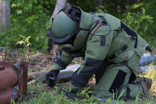 Staff Sgt. Joshua Papineau, an explosive ordnance disposal team leader with 68th CBRNE Ordnance Company from Fort Hood, Texas, uses a digital camera to document an explosive device during the 2018 Ordnance Crucible, June 6, 2018, at Fort A.P. Hill, Va. EOD teams are assessed on operations and associated tasks required to provide EOD support to unified land operations to eliminate and/or reduce explosive threats. The Ordnance Crucible is designed to test Soldiers' teamwork and critical thinking skills as they apply technical solutions to real world problems improving readiness of the force. (U.S. Army photo by Pfc. Christian Simmons)