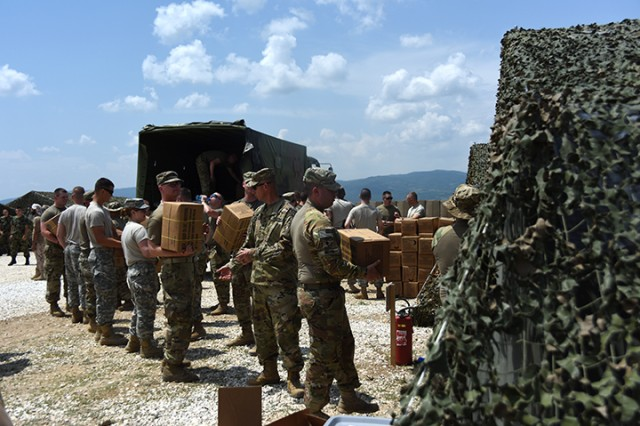 Members of the Ohio National Guard's 838th Military Police Company and the Tennessee National Guard's 269th Military Police Company unload Meals Ready to Eat, or MREs, during opening day of Exercise Platinum Wolf 2018 at Borovac Training Area, Serbia, June 11, 2018. The MP units arrived in the Republic of Serbia Sun., June 10, 2018, to participate in exercise Platinum Wolf. The two-week, multinational peacekeeping exercise, will bring 10 nations together to enhance military cooperation and interoperability at Serbia's South Base and Borovac Training Area, June 11 - 22.