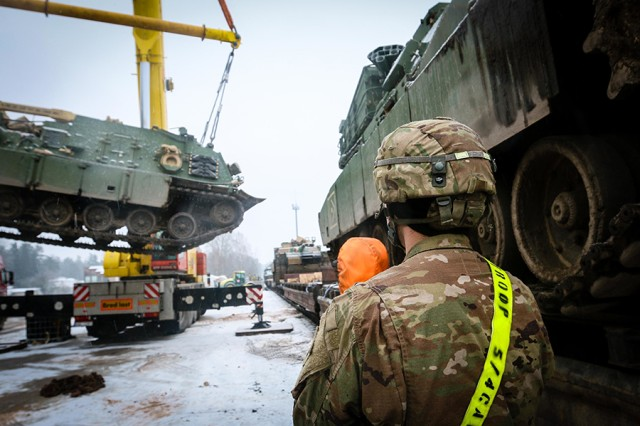 Pfc. Brandon DeFlippo, an M-1 Abrams tank system maintainer with the 5th Squadron, 4th Cavalry Regiment, 2nd Armored Brigade Combat Team, 1st Infantry Division, watches a recovery vehicle being lifted off of a train in Adazi, Latvia, on Dec. 7, 2017, as part of a readiness exercise in support of Atlantic Resolve.