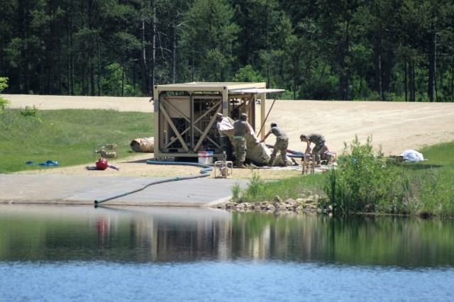 Soldiers at Fort McCoy, Wis., for training in the 86th Training Division's Combat Support Training Exercise 86-18-04 set up a reverse-osmosis water purification unit, or ROWPU, on South Post at Big Sandy Lake on June 7, 2018, at Fort McCoy, Wis. A ROWPU can provides potable water from any water source and can process up to 3,000 gallons an hour. A ROWPU can not only draw water from a lake, but also from rivers, oceans, or even holes in the ice. The system is built on to an Army trailer and includes its own generator and essentially a lab to operate the system from inside a covered enclosure. The system uses a variety of chemicals and membranes to filter and purify the water. Combat Support Training Exercise 86-18-04 is part of the Army Reserve's Combat Support Training Program, or CSTP. CSTP exercises are large-scale, collective-training exercises designed to immerse units into tactical training environments that closely replicate what they might experience in operational deployments. The 86th Training Division is a tenant organization at Fort McCoy. (U.S. Army Photo by Scott T. Sturkol, Public Affairs Office, Fort McCoy, Wis.)