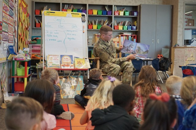 First Lt. Benjamin Francis, an infantry officer assigned to the 1st Battalion, 41st Infantry Regiment, 2nd Infantry Brigade Combat Team, 4th Infantry Division, reads to the students of Weikel Elementary, May 3, 2018, on Fort Carson, Colorado. (U.S. Army photo by 1st Lt. Brian Lee/1-41 UPAR)