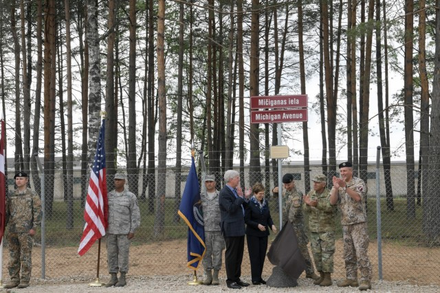 "Michigan Governor Rick Snyder, U.S. Ambassador to Latvia, Nancy Pettit, Adjutant General of Michigan, Maj. Gen. Gregory Vadnais, Latvian Armed Forces Commander, Lt. Gen. Leon�ds Kalni�s, and Latvian Infantry Brigade commander, Col. Ilm�rs Leji��, unveil ""Michigan Avenue"" at �da�i Military Base, Latvia, Tuesday, June 12, 2018, to commemorate the 25-year relationship between Latvia and Michigan under the U.S. National Guard Bureau's State Partnership Program (SPP). The event was also attended by U.S. and Latvian Military members. After the dedication, the distinguished visitors toured a construction work site where Michigan National Guard Engineers from the 110th Attack Wing, Battle Creek Air National Guard Base, Mich. have been operating as part of their annual Deployment for Training (DFT). The Civil Engineer Squadron is the fourth Air National Guard rotation supporting the 435th Construction and Training Squadron, Ramstein AB, Germany's project oversight. The U.S. Air Forces in Europe (USAFE) exercise-related construction projects are intended to provide temporary housing for participants from the United States and its Allies."