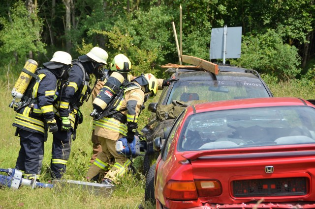 Fire fighters use a special tool to open a junk car that is used to simulate a crashed helicopter during a recent joint U.S. and host nation exercise June 7, 2017 at USAG Ansbach's Oberdachstetten training Area. (U.S. Army photo by Bianca Sowders, USAG Ansbach Public Affairs)