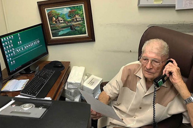 Alfred Budris conducts business at his desk at the Logistics Readiness Center Okinawa Office in  May. (Courtesy photo)