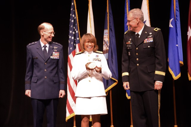 Air Force Maj. Gen. Bart O. Iddins (left), 59th Medical Wing commander, and Army Brig. Gen. George Appenzeller, Brooke Army Medical Center commander, present keynote speaker Vice Adm. Raquel Bono, director of the Defense Health Agency, with a US Navy Bicentennial Bronze medal during the San Antonio Uniformed Services Health Education Consortium graduation ceremony held June 7, 2018 at the Lila Cockrell Theatre in downtown San Antonio.  The front side of the coin is a Surface ship, aircraft carrier, fighter jet and submarine, while the reverse has the Flagship Alfred of the First American Fleet serving from 1775-1778 and the American eagle grasping an anchor.