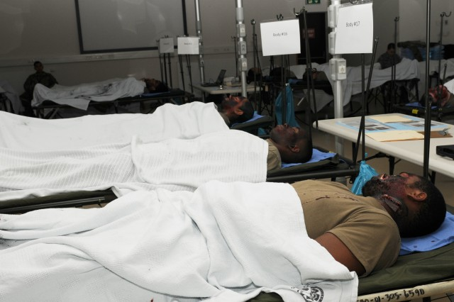 "Moulaged Soldiers lay in a simulated morgue as part of the Regional Health Command Europe's exercise Maroon Surge '18. Dental Soldiers, Airmen and NATO partners from around Europe worked together to identify ""remains"" after a simulated helicopter crash through forensic dentistry."