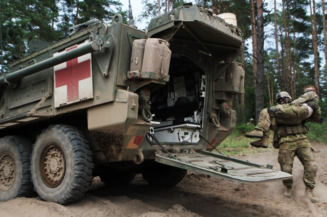 Staff Sgt. Westley Walker, platoon sergeant of 2nd platoon, Comanche Troop, 1st Squadron, 2nd Cavalry Regiment, Battle Group Poland, carries a soldier with a simulated combat injury to a medical evacuation vehicle in a combat training situation as part of their participation in Saber Strike 18 at the Bemowo Piskie Training Area on June 13, 2018. Saber Strike 18 is the eighth iteration of the long-standing U.S. Army Europe-led cooperative training exercise designed to enhance interoperability among allies and regional partners. (Michigan Army National Guard photo by Spc. Robert Douglas/ released).