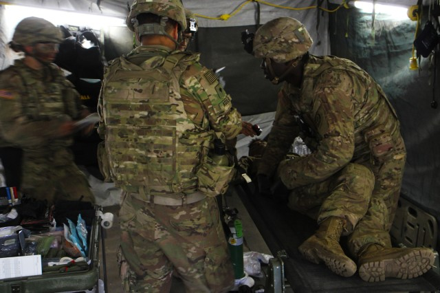 U.S. Army soldiers with the Headquarters and Headquarters Troop, 1st Squadron, 2nd Cavalry Regiment, perform a simulated medical examination during a combat training situation as part of their participation in Saber Strike 18 at the Bemowo Piskie Training Area on June 13, 2018. Saber Strike 18 is the eighth iteration of the long-standing U.S. Army Europe-led cooperative training exercise designed to enhance interoperability among allies and regional partners. (Michigan Army National Guard photo by Spc. Robert Douglas/ released).