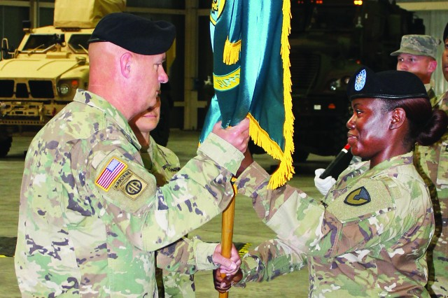 Lieutenant Col. Crystal Hills, outgoing commander, Army Field Support Battalion--Africa, passes the battalion colors to Col. Rodney H. Honeycutt, commander, 405th Army Field Support Brigade, at a change of command ceremony June 1 at Leghorn Army Depot in Livorno. Honeycutt then passed the colors to incoming commander, Lt. Col. Michelle Agpalza.