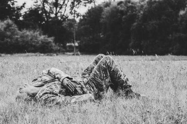 A service member assigned to the 306th Hospital Support Regiment based in York, England, lies in a field with simulated battle injuries waiting for the medical team to arrive at Swidwin Air Field in Swidwin, Poland, June 11, 2018.