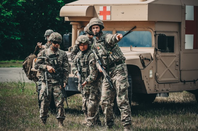 Soldiers assigned the 306th Hospital Support Regiment from York, England, give direction to U.S. service members at the mass casualty exercise at Swidwin Air Field in Swidwin, Poland, June 11, 2018.