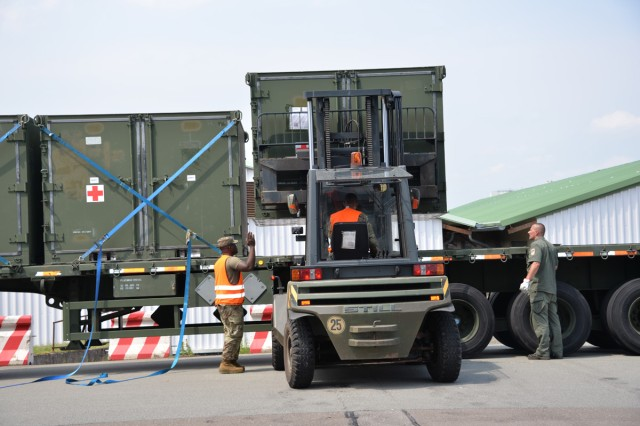 Staff Sgt. Lether Lofton, a USAMMCE medical support specialist, loads containers onto a flatbed trailer for transport.