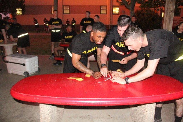Soldiers unscramble a mystery phrase at a table during the 2-4th FA Spiritual Fitness Olympiad, May 18, 2018. Soldiers received a line of the phrase after each event to complete the intended message.