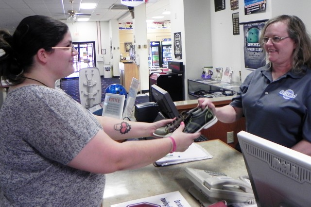 Left, Jessica Morse, food and drink supervisor at the Fort Sill Patriot Club, receives bowling shoes from TOBC manager Kelly Wright. Wright explained that employees of the FMWR may be employed by one organization, but help in other organizations as needed.