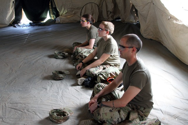 From front, Privates Kyle Lemieux, Autumn McDonald, and Santanna Dean, B/1-40th FA,  sit still in the Deployable Rapid Assembly Shelter, or DRASH tent, June 7, 2018, at the Teamwork Development Course. After a day of training outdoors, trainees stay in the 65-degree tent anywhere from 30 minutes to one hour to cool down.