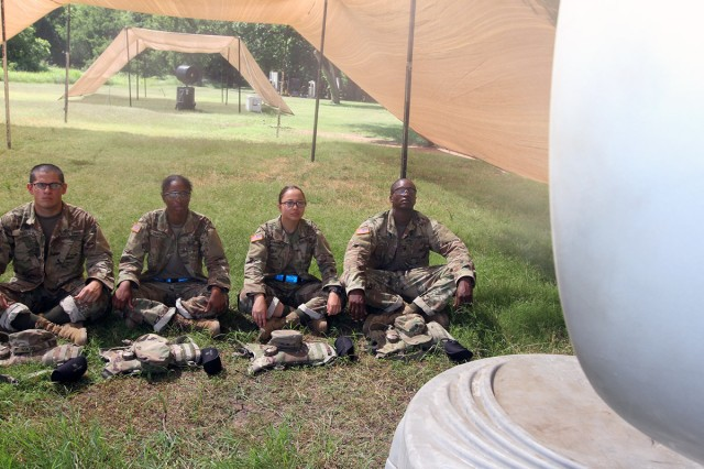 Trainees sit under a solar shield while a rotating misting fan blows over them June 7, 2018, at Fort Sill. The shield and fan are a couple methods used to prevent heat injuries during basic combat training.