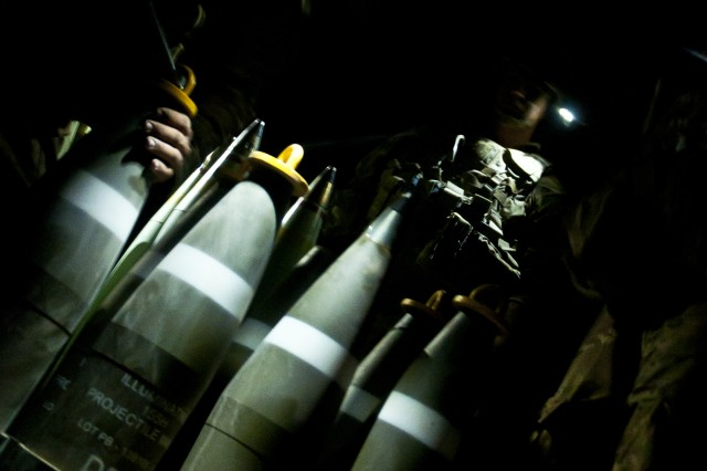 Coalition members prepare illumination artillery rounds to be fired at an outpost near Dashisha, Syria, June 8, 2018. The Coalition uses illumination rounds during Operation Roundup so the Syrian Democratic Forces can better see their objective as they advance against ISIS fighters. (U.S. Army photo by Staff Sgt. Timothy R. Koster)