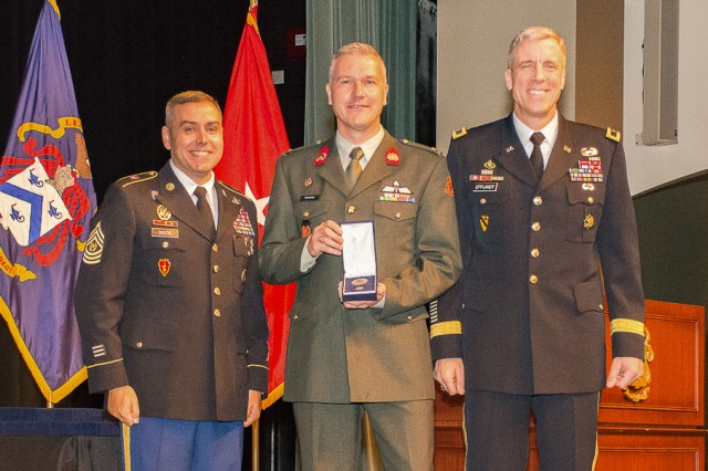 Netherlands Major Rene Berendsen receives the CGSC International Graduate Badge from Brig. Gen. Scott Efflandt, Provost of the Army University and Deputy Commandant of the Command and General Staff College, and Cmd. Sgt. Maj. Eric C. Dostie, Command Sergeant Major of the Combined Arms Center and the Command and General Staff College.