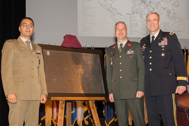 Majors Stefano Catania, Italy (l), and Rene Berendsen, Netherlands, present the International Military Student Class of 2018 gift to Brig. Gen. Scott Efflandt during the International Military Student Badge Ceremony June 14.