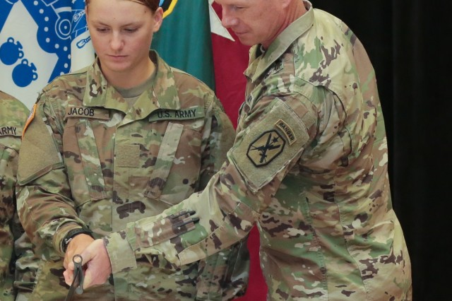 FORT BENNING, Ga. (June 14, 2018) - Pvt. Emmaleigh Jacob, left, Echo Company, 2nd Battalion, 58th Infantry Regiment, one of the most junior Soldiers on post, makes the second cut of the cake with Maneuver Center of Excellence Command Sgt. Maj. Scott A. Brzak. The Maneuver Center of Excellence held a cake-cutting ceremony June 14 at the headquarters at Fort Benning, Georgia, in celebration of the 243rd anniversary of the U.S. Army's founding in 1775. (U.S. Army photo by Markeith Horace, Maneuver Center of Excellence, Fort Benning Public Affairs)