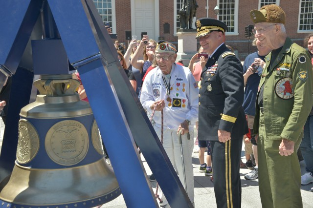 Philadelphia - Maj. Gen. Troy D. Kok, commanding general of the 99th Readiness Division, U.S. Army Reserve, rings the Freedom Bell with a Pearl Harbor survivor here June 14, 2018, in honor of the 243rd Army Birthday. Service members and visitors were given the opportunity to ring The Freedom Bell during Philadelphia's Stripes and Stars Festival.