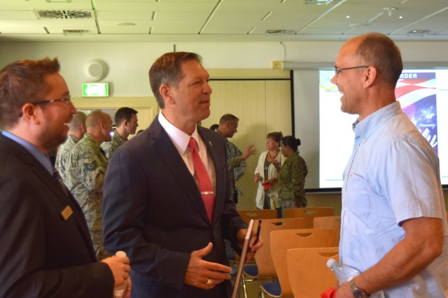 Thomas C. Joyce, deputy to the garrison commander for U.S. Army Garrison Benelux, speaks with community members after the town hall at Geilenkirchen Air Base in Germany, June 6, 2018. Garrison leadership was on hand to answer questions about Schinnen's 2019 move to Brunssum.