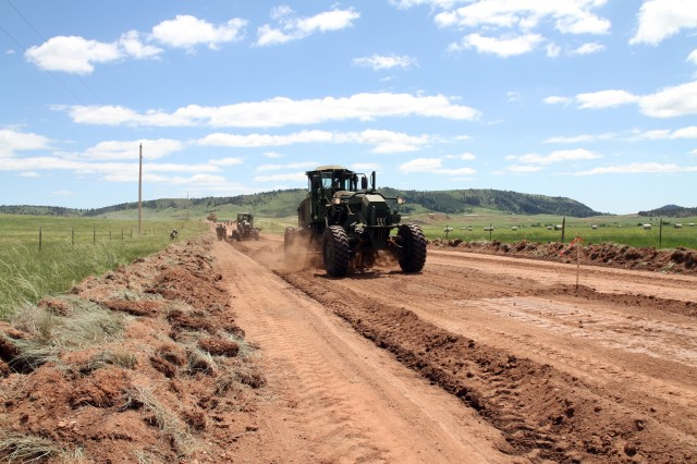 A heavy equipment operator in South Dakota Army National Guard's 842nd Engineer Company, grades a road in Wind Cave National Park, S.D., June 12, 2018. Their mission is to improve the road to expand public access at the park.