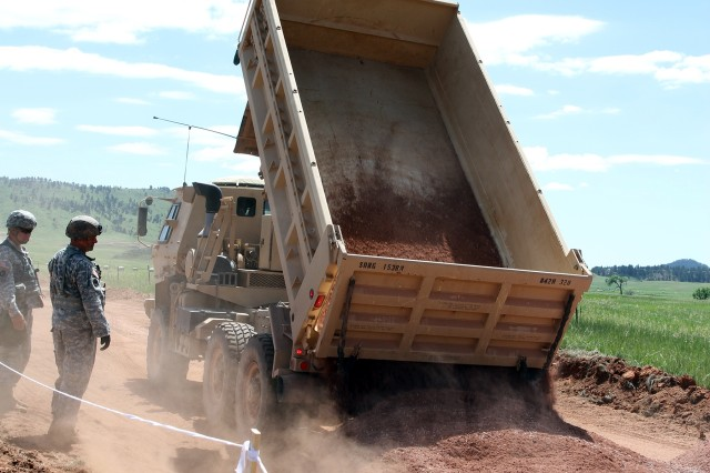 Soldiers of the South Dakota Army National Guard's 842nd Engineer Company, dump a load of gravel in Wind Cave National Park, S.D., June 12, 2018. Their mission is to improve the road to expand public access at the park.