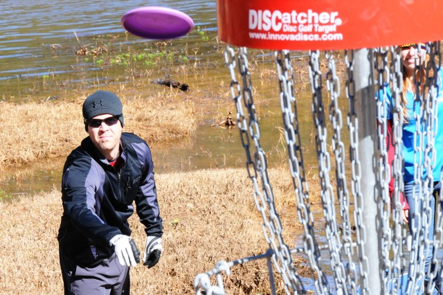 Then-CW4 Bryan Topham takes a throw at one of the baskets on the disc golf course in this file photo.