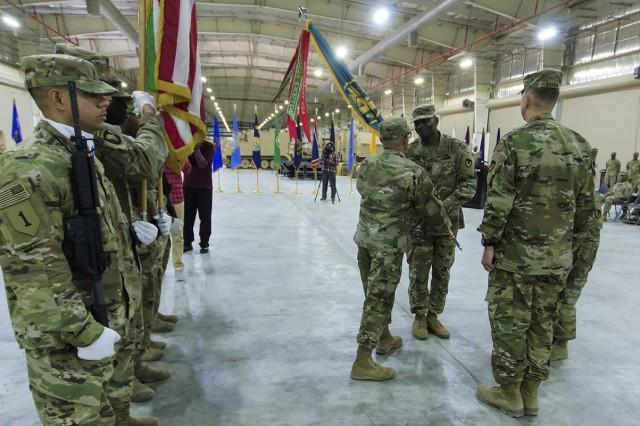 Sgt. Maj. Larry Montes, sergeant major, Army Field Support Battalion-Kuwait, passes the unit colors to Lt. Col. Mike Jordan, outgoing commander, AFSBn-Kuwait for the last time during a change of command ceremony for the AFSBn-Kuwait at Camp Arifjan, Kuwait, June 15. (U.S. Army Photo by Justin Graff, 401st AFSB Public Affairs)