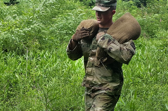 "A second lieutenant carries sandbags during Operation ""OBJ BUILD."""