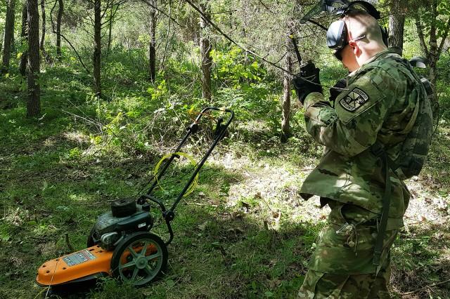 "2nd Lt. Mitchell Beekman monitors radio communications while working the ""brush hog."""